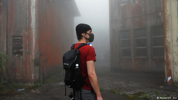 man with backpack and surgical mask between ruins (Reuters/T. Siu)