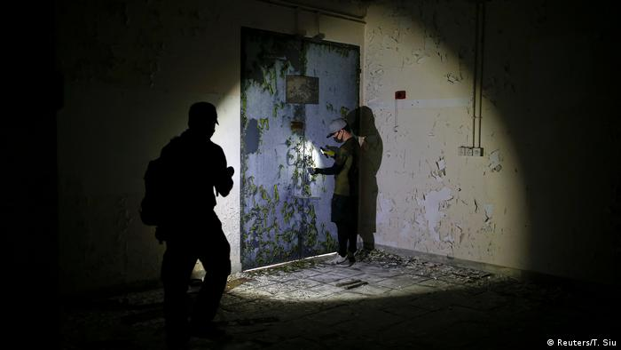 A man shines a flashlight at another man about to open a door (Reuters/T. Siu)