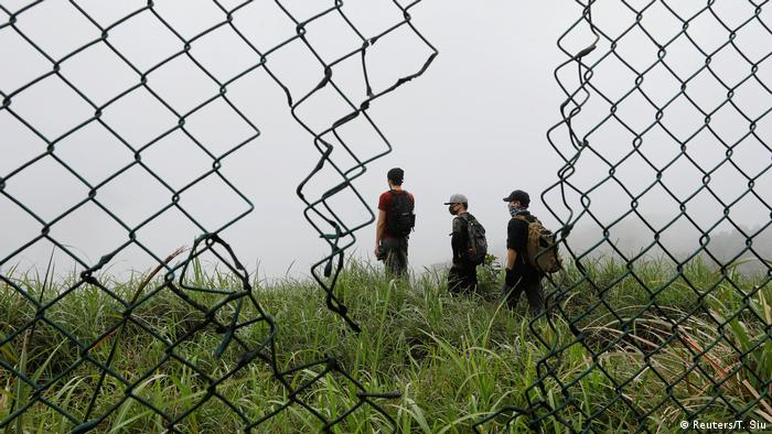 Wire mesh fence with tear, three people in the background (Reuters/T. Siu)