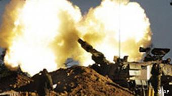 Israeli Army soldiers take cover as a mobile artillery piece fires towards targets in the southern Gaza Strip