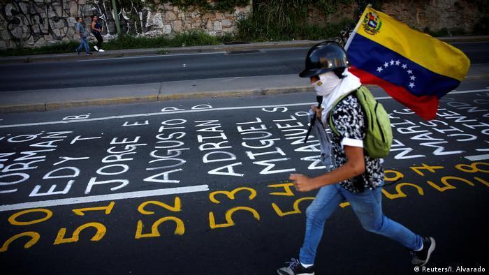Un manifestante camina junto a la lista de víctimas de la violencia durantes las manifestaciones.