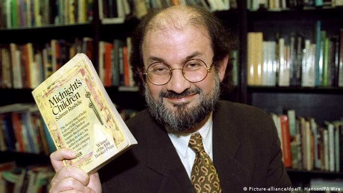 Salman Rushdie holding his novel Midnight's Children (Picture-alliance/dpa/F. Hanson/PA Wire)