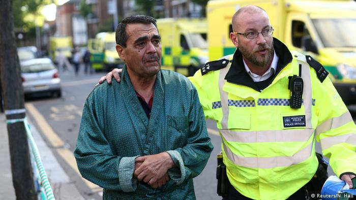 Ein Polizist betreut einen geretteten Bewohner des Hochhauses in London (Reuters/N. Hall)