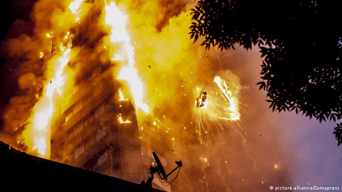 Debris falls from the burning Grenfell Tower