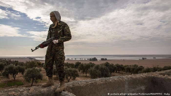 A soldier of the Kurdish YPG, which forms part of the SDF, stands near Tabqa, roughly 50 kilometers away from Raqqa