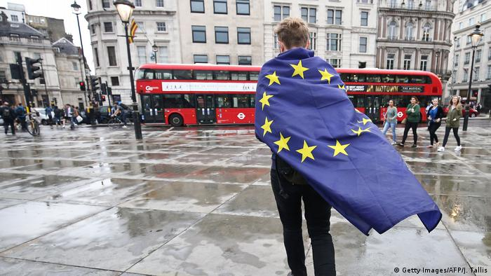 A person wrapped in an EU flag in London looks at a double-decker bus (Getty Images/AFP/J. Tallis)