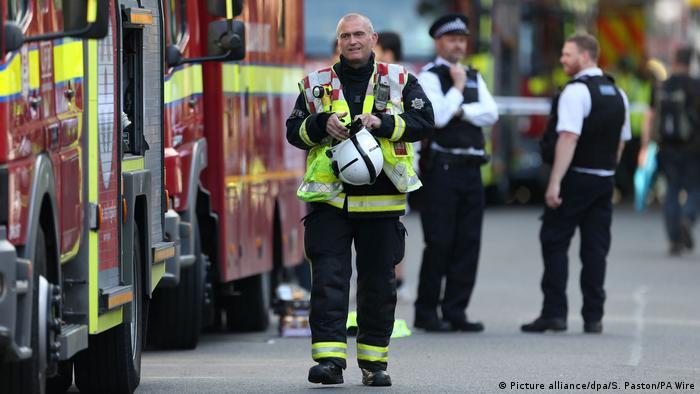 A firefighter stands near fire trucks outside Grenfell Tower