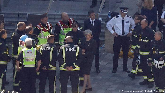 May standing with firefighters and police at the site of the London fire (Picture-Alliance/AP Photo/F. Augstein)