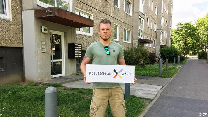 Michel Honauer, in Dresden, holding a DW placard saying #DeutschlandWählt, meaning Germany votes.