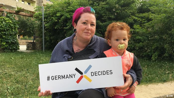 Carmen and her daughter holding a sign that says Germany Decide