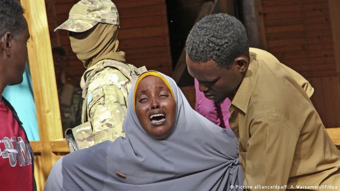 Eine weinende Frau wird von einem Mann in Uniform getröstet
