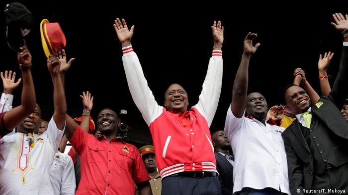 Uhuro Kenyatta raises his arms to greet his supporters at a rally