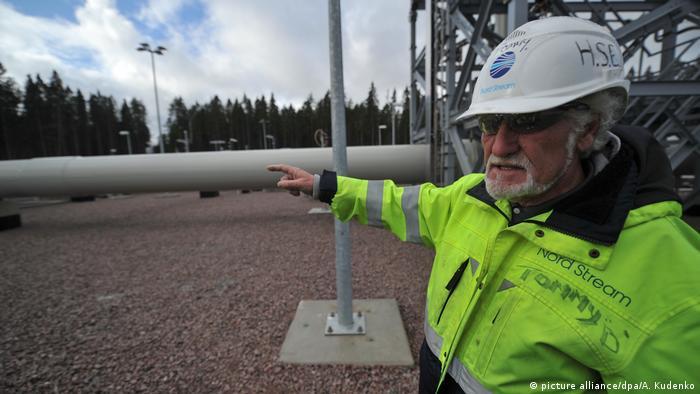 Человек показывает рукой в сторону строящегося газопровода Сверный поток-2