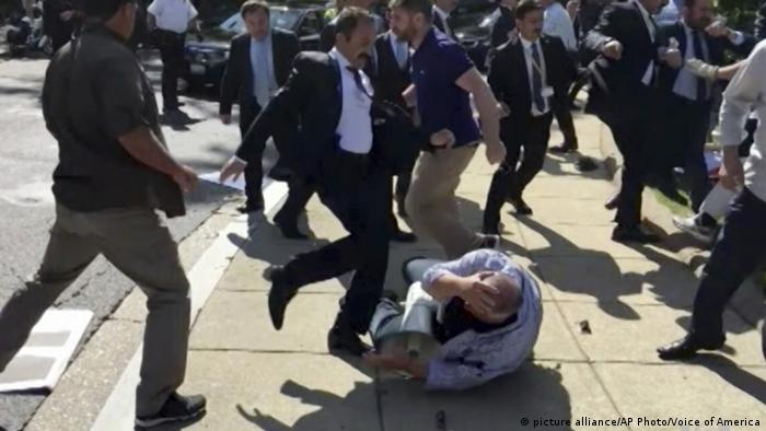 A member of Erdogan's secruity detail kicks a man lying on the ground