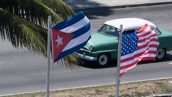 Carro antigo passa em uma rua. Em primeiro plano, uma bandeira dos EUA e uma bandeira de Cuba tremulando.