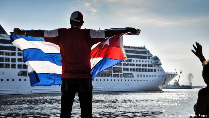 Мужчина с кубинским флагом на фоне круизного лайнера