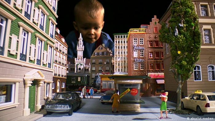 Film München - Geheimnisse einer Stadt - Szene mit einem kleinen Jungen, der sich über eine Spielzeugstadt beugt (absolut medien)