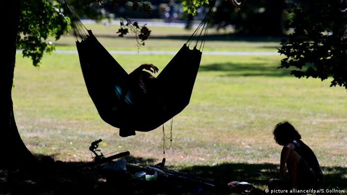 A backlit person in a hammock and another reading outside (picture alliance/dpa/S.Gollnow)