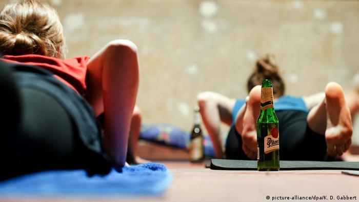 Teilnehmer eines Bieryoga-Kurses praktizieren eine Yogaübung mit Bierflasche (Foto: dpa)