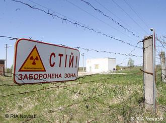 Barbed wire and a radioactivity sign block passage onto a field in the exclusion zone around Chernobyl