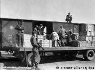 In 1946, workers load looted art onto a truck