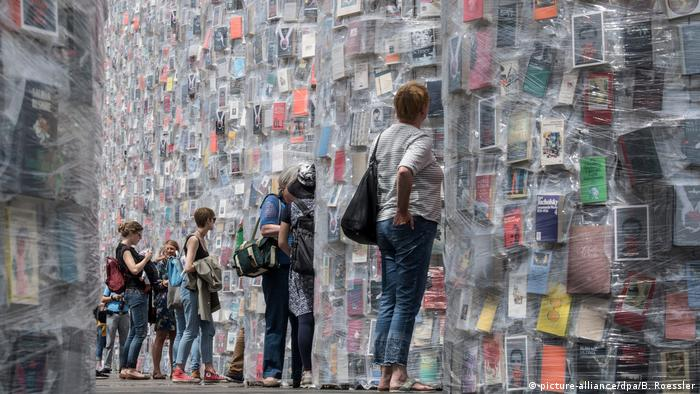 Visitors peer at books taped to the column of the Parthenon (picture-alliance/dpa/B. Roessler)