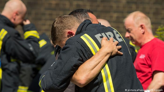 firefighters embrace (picture-alliance/dpa/D. Lipinski)