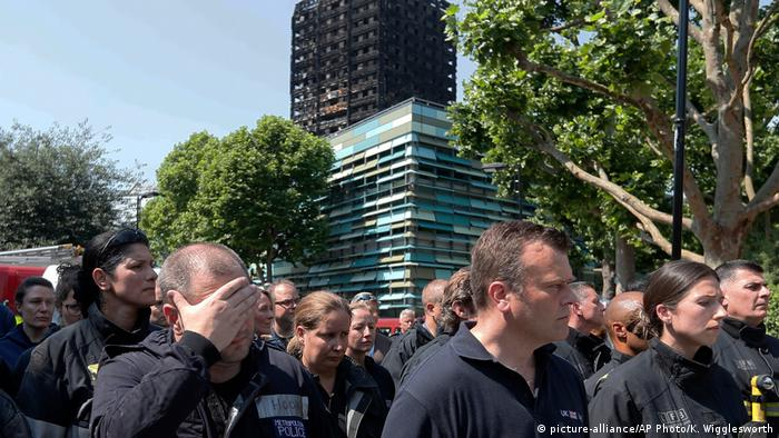 Firefighters observe a minute's silence in the shadows of Grenfell Tower, a social housing block in the wealthy borough of Kensington that burnt down in July 2017. 71 people lost their lives.