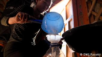 A young woman pours camel milk into a bottle inside her ger, a typical nomad's tent in Mongolia (Photo: Jacopo Pasotti)