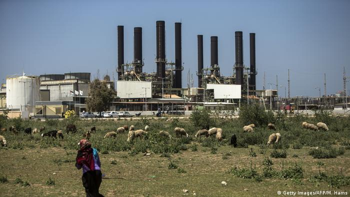 A Palestinian woman walks past the Nuseirat power plant in the Gaza Strip