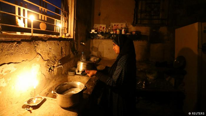 A woman in Gaza cleans by candlelight (REUTERS)