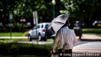 A man uses an umbrella to shield himself from the sun while walking through the park by Union Station on August 12, 2016 in Washington, D.C. Photo credit: Getty Images/G.Demczuk.