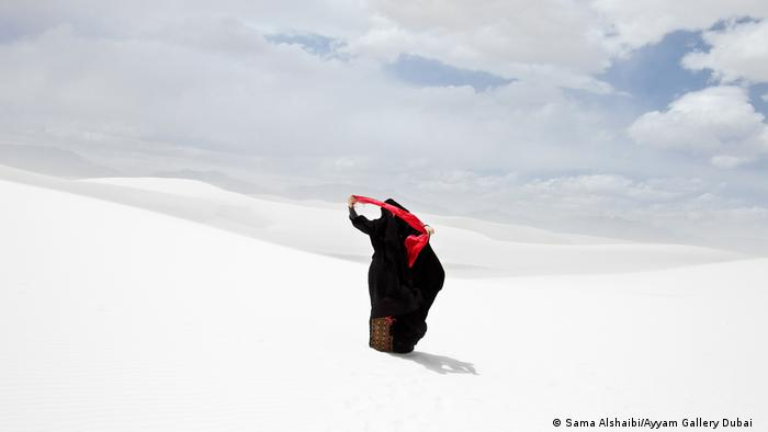 woman walking on white sand, in black, bright red scarf