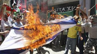 Demonstrators burn an Israeli flag during a protest against Israel's military strikes on the Gaza Strip