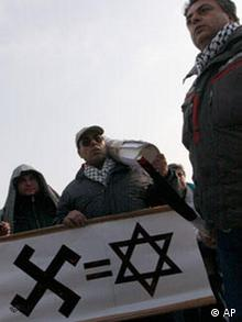 Protesters hold a banner with swastika and a star of David, during a protest against the Israeli offensive in Gaza