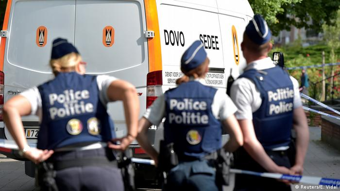 Belgian police stand guard during a house search