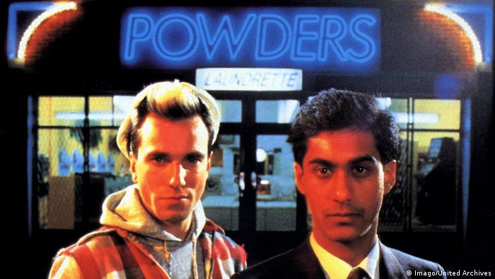 Film still My beautiful Laundrette with two young men standing in front of a shop named Powders Laundrette (Imago/United Archives)