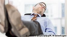 ILLUSTRATION - Ein Mann schläft am 14.04.2014 in einem Büro in Berlin an seinem Schreibtisch. | Verwendung weltweit