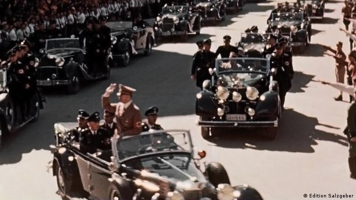 Adolf Hitler addressing a crowd while riding in a car