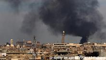 Smoke billows from behind the Great Mosque of al-Nuri in Mosul's Old City on April 17, 2017, during an offensive by Iraqi security forces to recapture the city from Islamic State (IS) group fighters. / AFP PHOTO / AHMAD AL-RUBAYE (Photo credit should read AHMAD AL-RUBAYE/AFP/Getty Images)