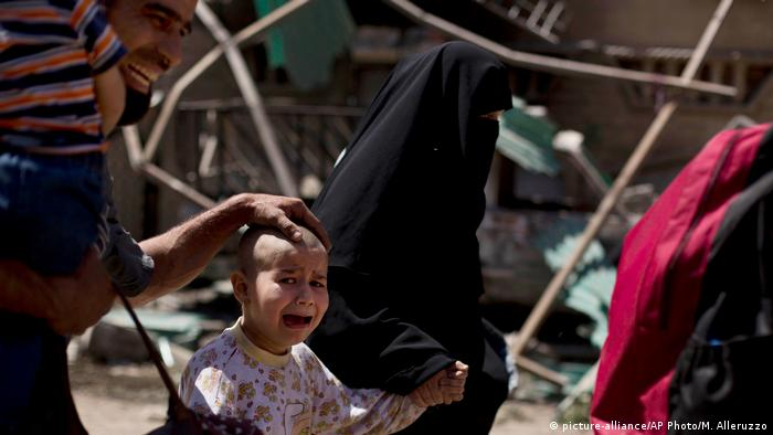 a girl with a shaved head and her father cry as the family flees the al-Rifai neighborhood (picture-alliance/AP Photo/M. Alleruzzo)