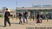 Ein Gruppe junger Männer verlässt am 23.02.2017 in Begleitung eines Polizisten das Flughafengebäude in Kabul (Afghanistan). Einige versuchen ihr Gesicht zu verbergen. Erneut sind abgelehnte Asylbewerber von Deutschland nach Afghanistan abgeschoben worden. Das Flugzeug mit 18 Flüchtlingen an Bord erreichte Kabul aus München kommend am Donnerstagmorgen. Foto: Mohammad Jawad/dpa Foto: Mohammad Jawad/dpa | Verwendung weltweit