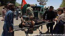 22.06.2017*****Afghan men carry a victim of a powerful car bomb in Lashkar Gah, the capital of Helmand province, on June 22, 2017. Twenty people were killed June 22 when a powerful car bomb struck a bank in Afghanistan's Lashkar Gah city as government employees were queueing to withdraw salaries, the latest bloody attack during the holy month of Ramadan. / AFP PHOTO / NOOR MOHAMMAD (Photo credit should read NOOR MOHAMMAD/AFP/Getty Images)