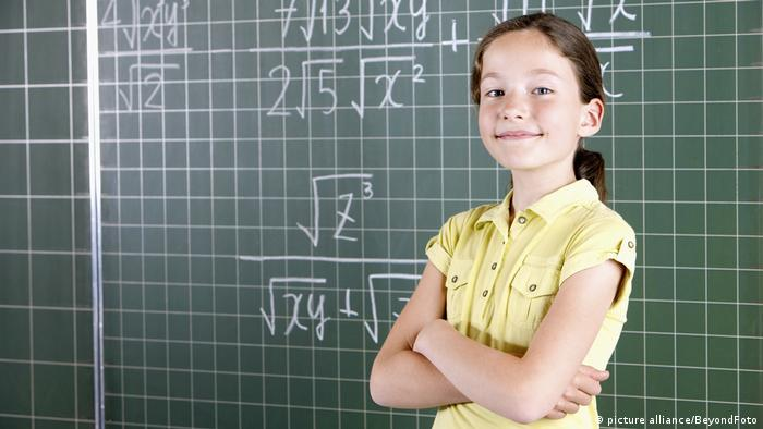 Girl standing in front of chalkboard (picture alliance/BeyondFoto)