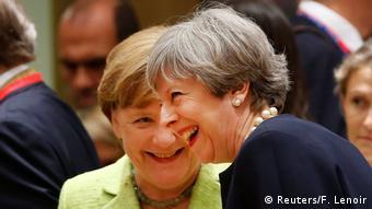 Theresa May and Angela Merkel laughing at EU summit