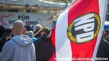 ARCHIV - Ein Teilnehmer einer NPD-Kundgebung trägt am 01.05.2016 in Schwerin (Mecklenburg-Vorpommern) eine NPD-Fahne. Bundesinnenminister Thomas de Maizière (CDU) hat das Verfahren eingeleitet, mit dem der rechtsextremen NPD die Parteienfinanzierung entzogen werden soll. (zu dpa:De Maizière:Verfahren zumStopp der NPD-Finanzierung eingeleitet vom 07.04.2017) Foto: Jens Büttner/dpa-Zentralbild/dpa +++(c) dpa - Bildfunk+++ | Verwendung weltweit