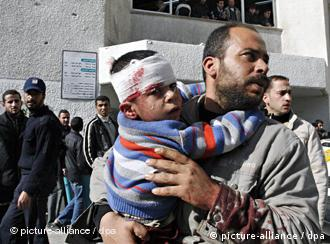 A Palestinian man carries his bleeding child following an Israeli airstrike on the Gaza Strip