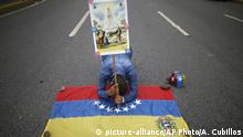 Anti-government protester prays while kneeling on a Venezuelan flag.(AP Photo/Ariana Cubillos)