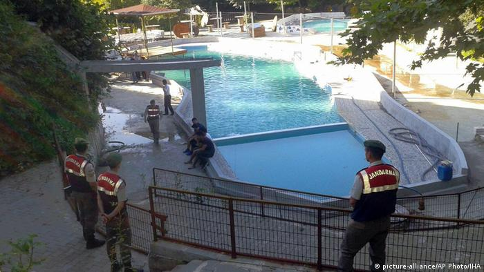 Paramilitary police officers investigate after five people were caught up in an electrical current in the pool (picture-alliance/AP Photo/IHA)