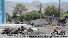 23.06.2017 *** QUETTA, PAKISTAN - JUNE 23 : A man rides rides a motorcycle past the wreckage of a car and a road at the site of suicide bomb blast in Quetta, Pakistan on June 23, 2017. At least 12 people were killed and 16 injured in a suicide attack near the office of inspector General Balochistan police on Shuhada Chowk Gulistan Road. Mazhar Chandio / Anadolu Agency |